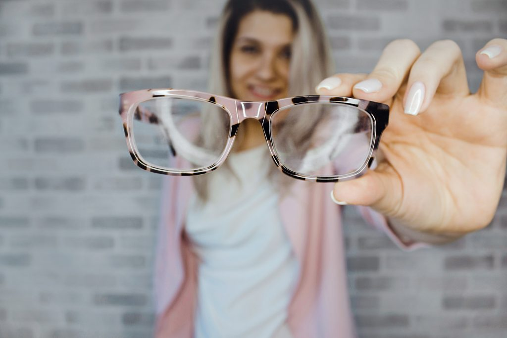 Picture of a woman holding pink eyeglasses.
